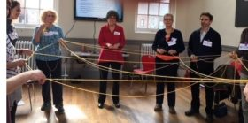 people standing with twine showing the Web of Injustice